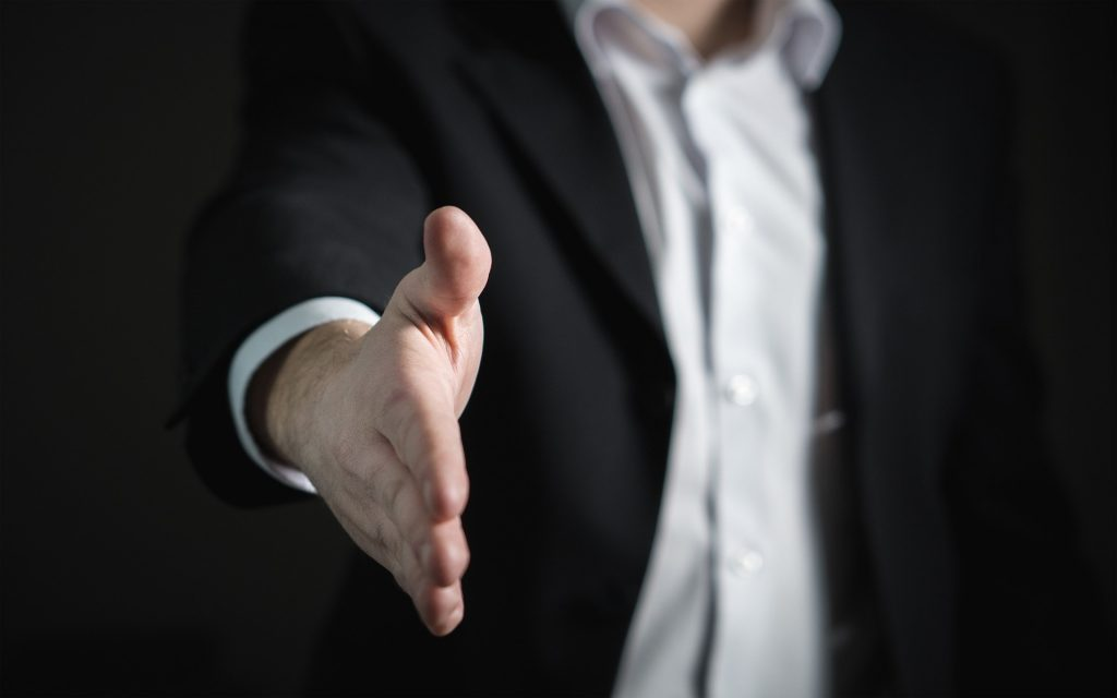 man in suit shaking hand